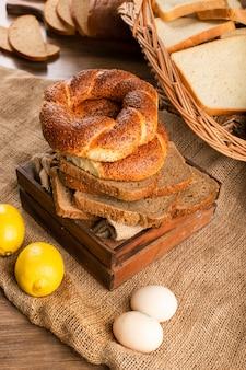 Bagels met sneetjes brood in doos en citroenen