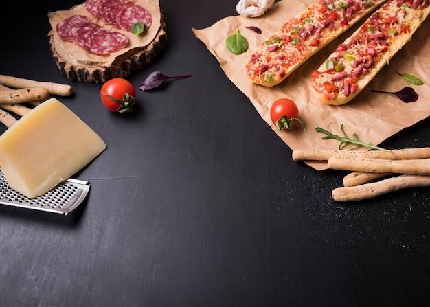 Baguettepizza met italiaanse voedselingrediënten over zwarte steenoppervlakte