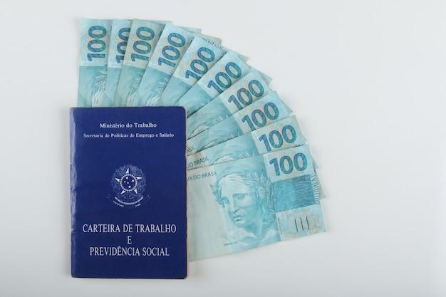 Bahia, brazilië. agosto 27, 2021. braziliaanse werkkaart (carteira de trabalho) en braziliaans geld. vertaling: federale republiek brazilië, ministerie van arbeid. werkboekje en social welfare..