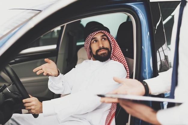 Bahreinse man en dealer voertuig kiezen in salon.