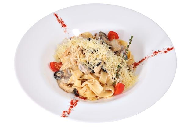 Bak pasta fettuccine met kip en champignons, op een witte plaat, geïsoleerd op een witte achtergrond.