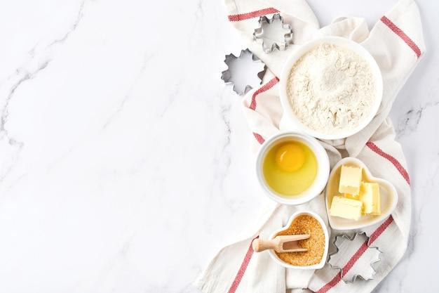 Bakachtergrond met bloem, eieren, keukengerei, keukengerei en koekjesvormen op witte tafel