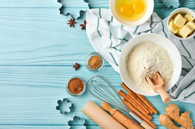 Bakachtergrond met ingrediënten voor het maken van peperkoekmeel, eieren, keukengerei, gebruiksvoorwerpen en koekjesvormen op blauwe houten tafel. bovenaanzicht. platliggende stijl. bespotten. kerst bakken.