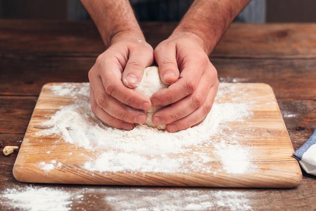 Baker bedrijf rauw deeg in handen close-up