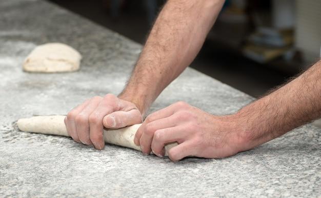 Baker bereidt brooddeeg voor, dicht omhoog op zijn handen