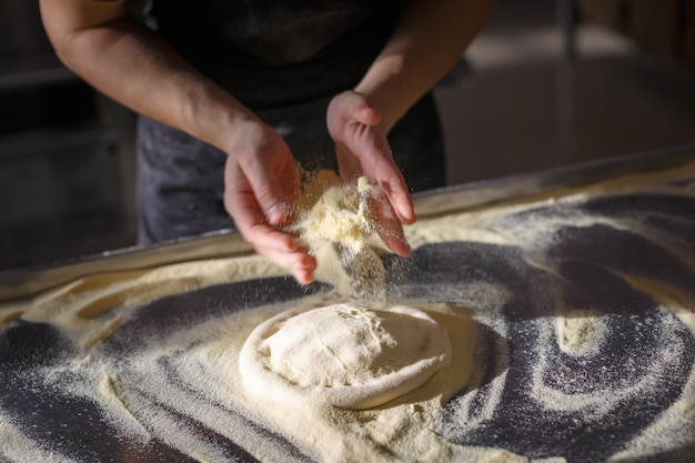 Baker bestrooit deeg voor pizza door griesmeel