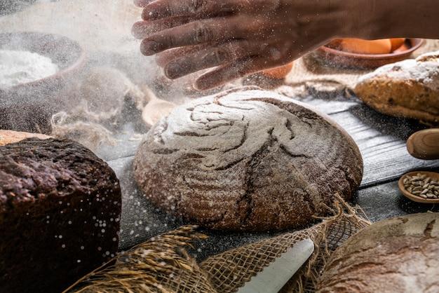 Baker brood koken. de vrouw slaat bloem over het deeg.