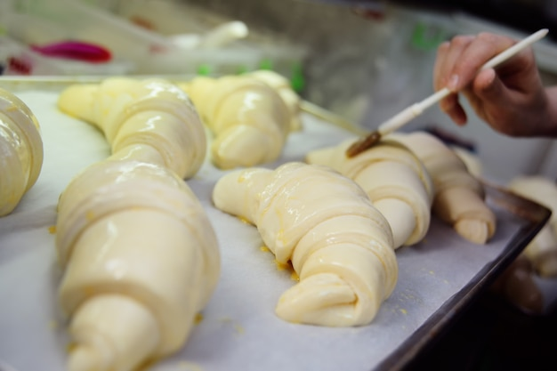 Baker butters rauwe croissants in close-up voor het bakken