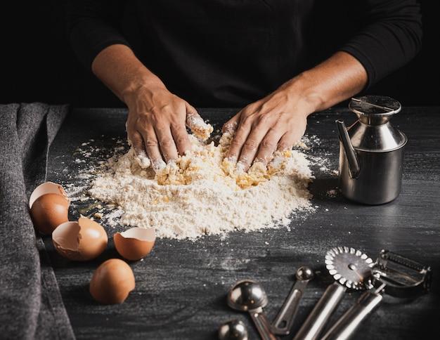 Baker die deeg naast bakkerijhulpmiddelen mengen