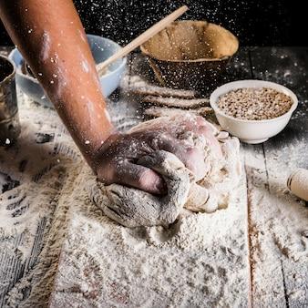 Baker die het tarwebloem op het deeg over de keukenlijst uitsprenge