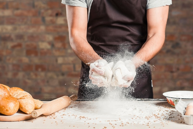 Baker die kneeddeeg met bloem op het werkblad van de keuken mengen