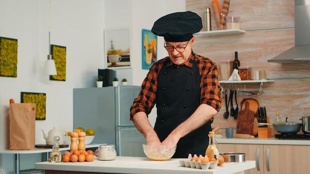 Baker kending deeg in keukentafel met schort en bonete. gepensioneerde oudere chef-kok met uniform besprenkelen, zeven zeven van rauwe ingrediënten met de hand bakken zelfgemaakte pizza, brood.