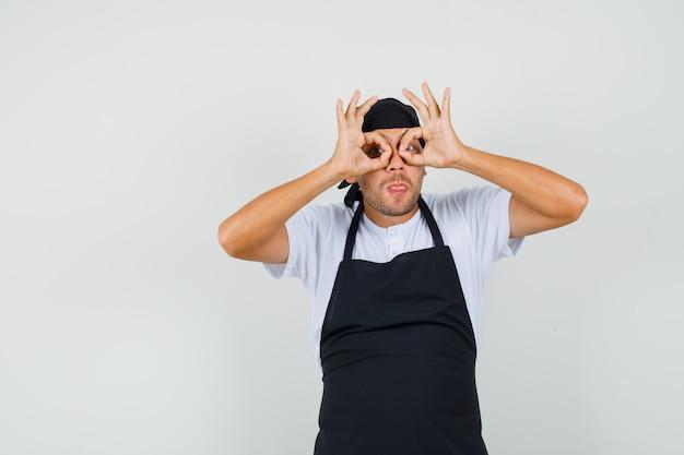 Baker man bril gebaar tonen, tong in t-shirt uitsteekt