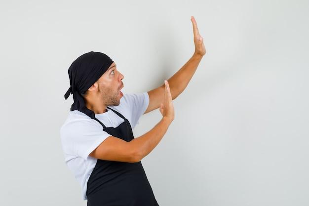 Baker man houden handen op beschermende wijze in t-shirt
