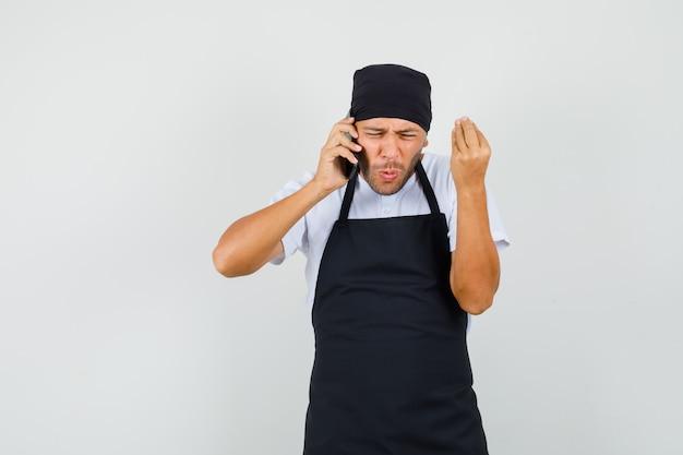 Baker man iets op mobiele telefoon in t-shirt bespreken