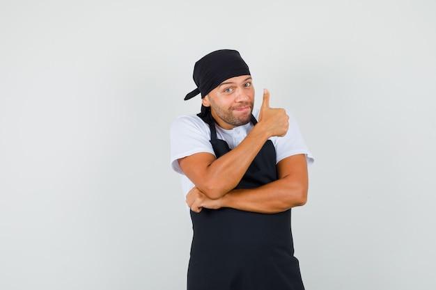 Baker man in t-shirt, schort duim opdagen en blij kijken