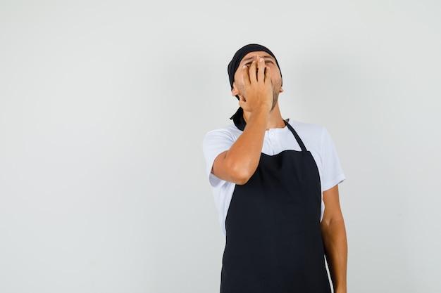 Baker man in t-shirt, schort geeuwen en slaperig kijken
