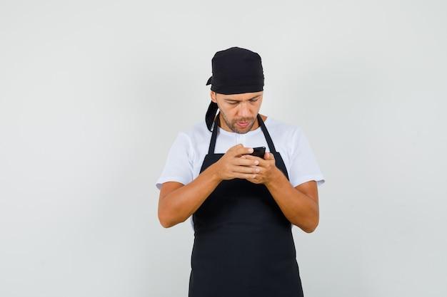 Baker man in t-shirt, schort met behulp van mobiele telefoon en bezig kijken