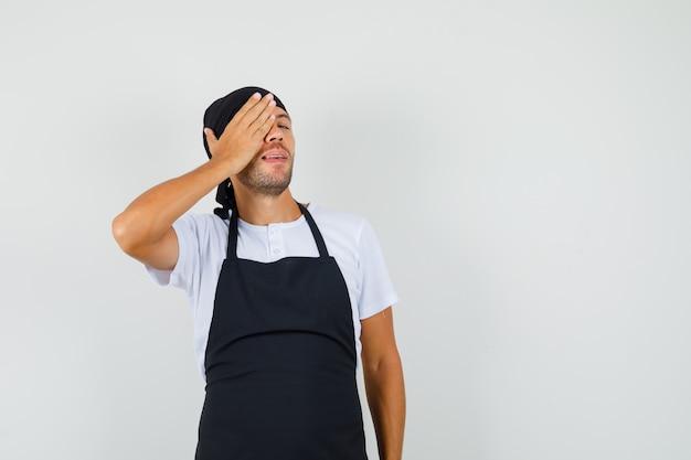 Baker man in t-shirt, schort met hand op één oog