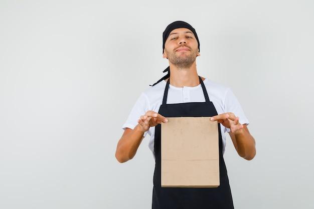 Baker man in t-shirt, schort met papieren zak en trots op zoek