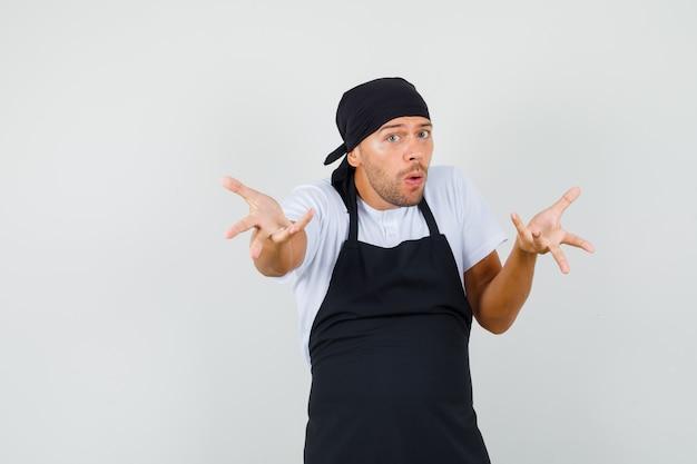 Baker man in t-shirt, schort strekken handen in vragend gebaar en op zoek verward