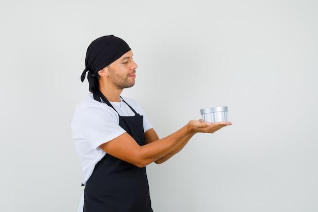 Baker man kijken naar geschenkdoos in zijn handpalmen in t-shirt