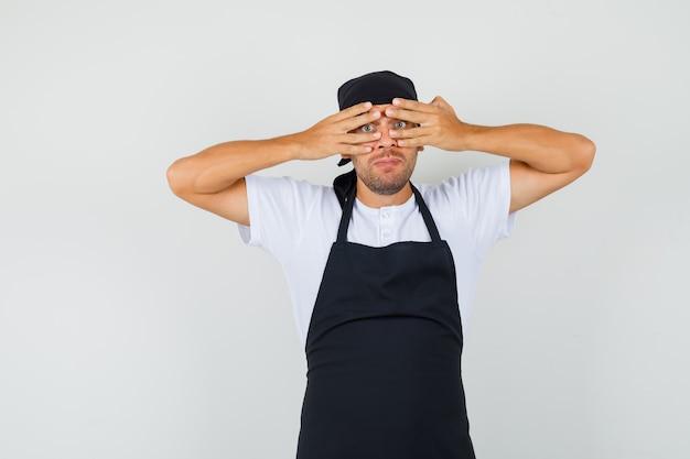 Baker man kijkt door vingers in t-shirt