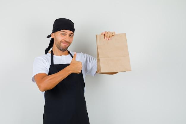 Baker man met papieren zak, duim opdagen in t-shirt