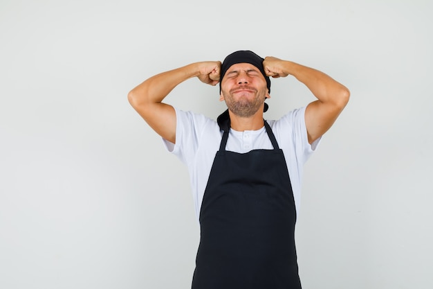 Baker man met vuisten aan het hoofd in t-shirt