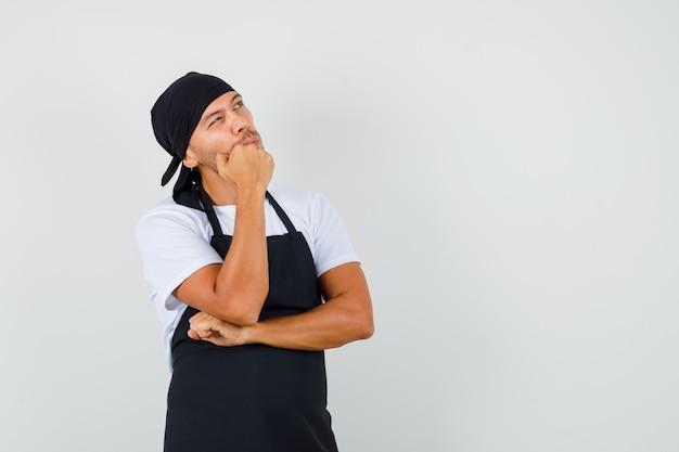 Baker man opzoeken in t-shirt, schort en peinzend kijken
