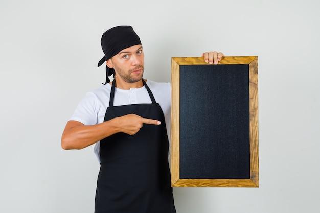 Baker man wijzend op bord in t-shirt