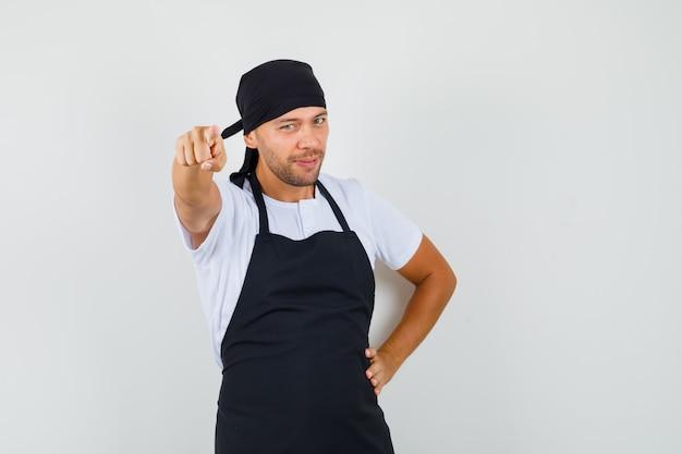 Baker man wijzend op camera in t-shirt, schort en op zoek zelfverzekerd