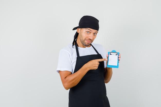 Baker man wijzend op mini klembord in t-shirt, schort en kijkt optimistisch
