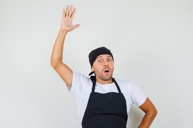 Baker man zwaaiende hand om afscheid te nemen in t-shirt