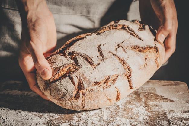 Baker of chef-kok die vers gemaakt brood houdt
