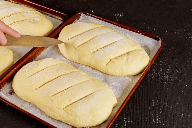 Baker snijdt ongekookt brooddeeg op rek klaar om te bakken