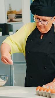 Baker verspreidt meel op houten tafel thuis in moderne keuken met schort en bonete. gelukkige bejaarde chef-kok met uniform besprenkelen, zeven, zeven, zeven, rauwe ingrediënten, met de hand bakken van zelfgemaakte pizza