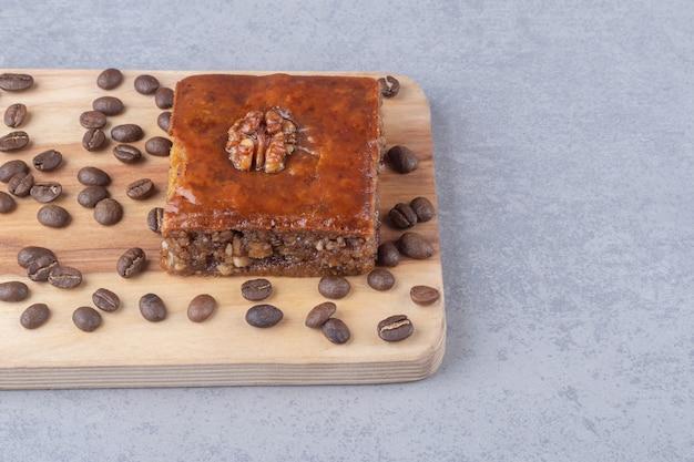Bakhlava en koffiebonen op een houten bord op marmeren tafel.