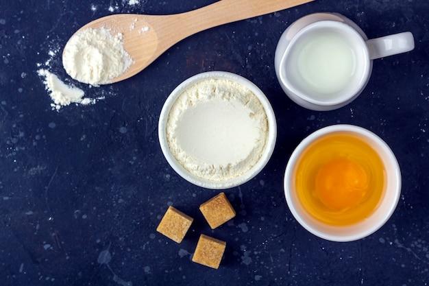 Bakken achtergrond. ingrediënten en gebruiksvoorwerpen voor het koken van cake op donkere tafel. voedsel concept.