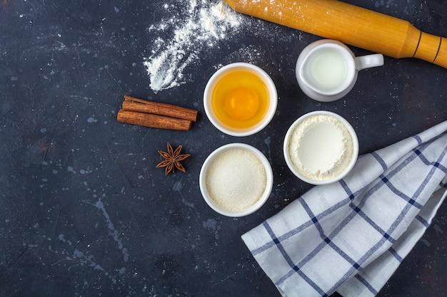 Bakken achtergrond. ingrediënten en keukengerei voor het koken van cake (meel, ei, melk, suiker, deegroller, handdoek) op donkere tafel. voedsel concept. close-up, kopieer ruimte voor tekst.
