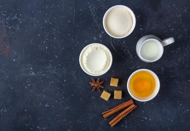 Bakken achtergrond. ingrediënten voor het koken van cake in kommen op donkere tafel. voedsel concept.