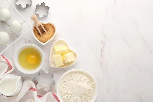 Bakken achtergrond met bloem, eieren, keukengerei, gebruiksvoorwerpen en koekjesvormen op witte marmeren tafel. bovenaanzicht. platliggende stijl. bespotten.
