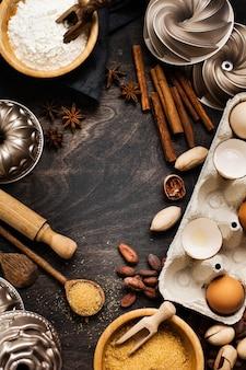 Bakken en culinair met bloem, suiker, kruiden, noten, kaneel, houten lepels en deegroller op een oude donkere houten