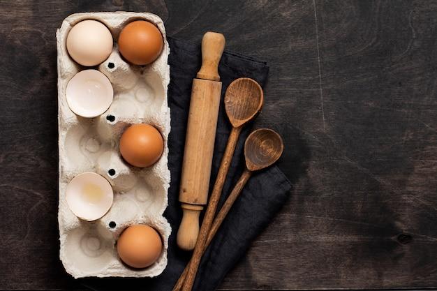 Bakken en culinaire wand. veelkleurige kippeneieren en schelpen in oude cellulose vintage container met bloem, suiker, houten lepels en een deegroller op oude donkere houten muur. bovenaanzicht.