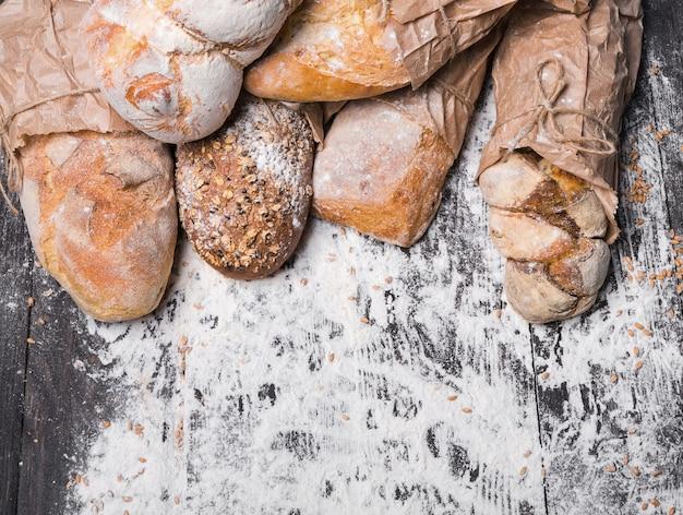 Bakken en koken concept achtergrond. rand van verschillende soorten brood, verpakt in ambachtelijk papier bovenaanzicht met kopie ruimte op houten tafel, besprenkeld met bloem.