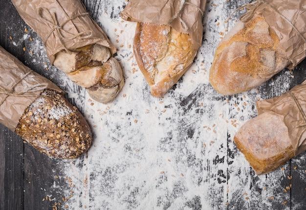 Bakken en koken concept achtergrond. veel verschillende soorten brood, verpakt in bovenaanzicht van ambachtelijk papier met kopie ruimte in het midden op houten tafel, bestrooid met bloem.