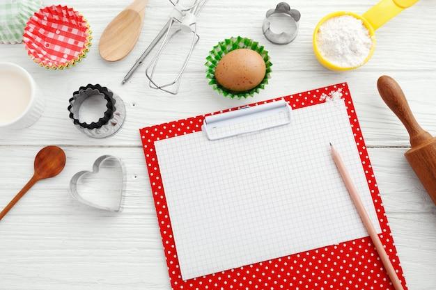 Bakken gebruiksvoorwerpen en ingrediënten met rode klembord, bovenaanzicht