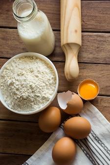 Bakken ingrediënten meel, eieren, open dooier, melk, deegroller, linnen handdoek, rustieke keuken interieur