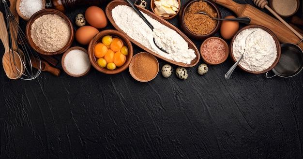 Bakken ingrediënten voor deeg op zwart, bovenaanzicht van meel, eieren, boter, suiker voor zelfgemaakte bakken met kopie ruimte voor tekst