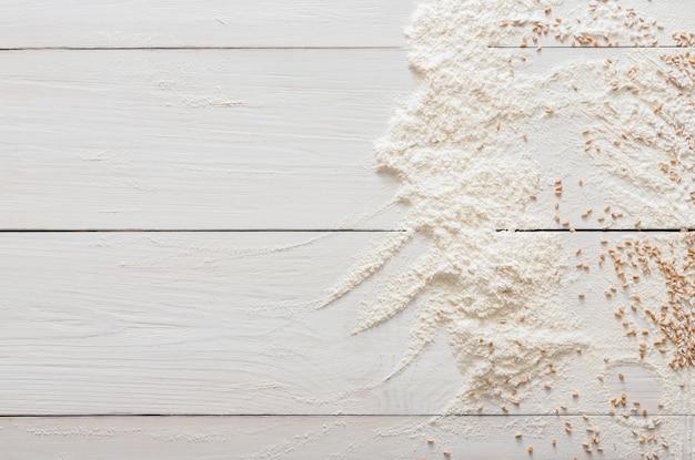 Bakken klasse of recept concept op witte houten tafel, bestrooid tarwemeel en graan. bovenaanzicht op houten tafel. koken van deeg of gebak.